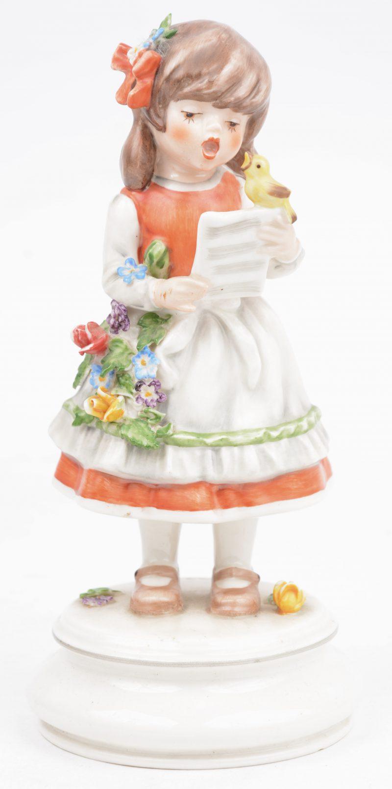 """""""Zingend meisje met vogeltje"""". Een meerkleurig porseleinen beeldje. Onderaan gemerkt, genummerd 585/2000 en gedateerd 1975."""