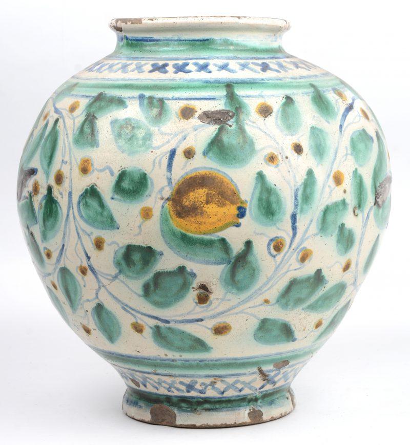 Een aardewerken vaas in de stijl van Iznik met een polychroom decor van bladeren en bloemen. Randslijtage.