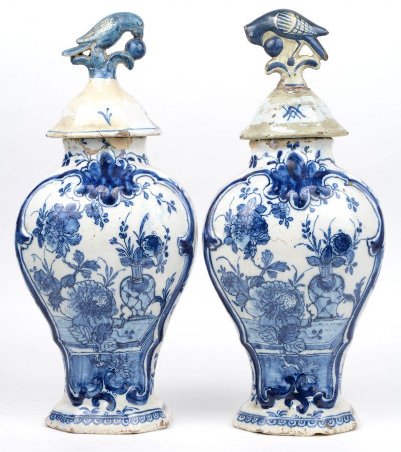 Een paar dekselvazen in Lodewijk XV-stijl in blauw en wit versierd met bloementafels in uitsparingen. Delft, XVIIIde eeuw. Merk van de Clauw. Letsels en herstelde deksels.