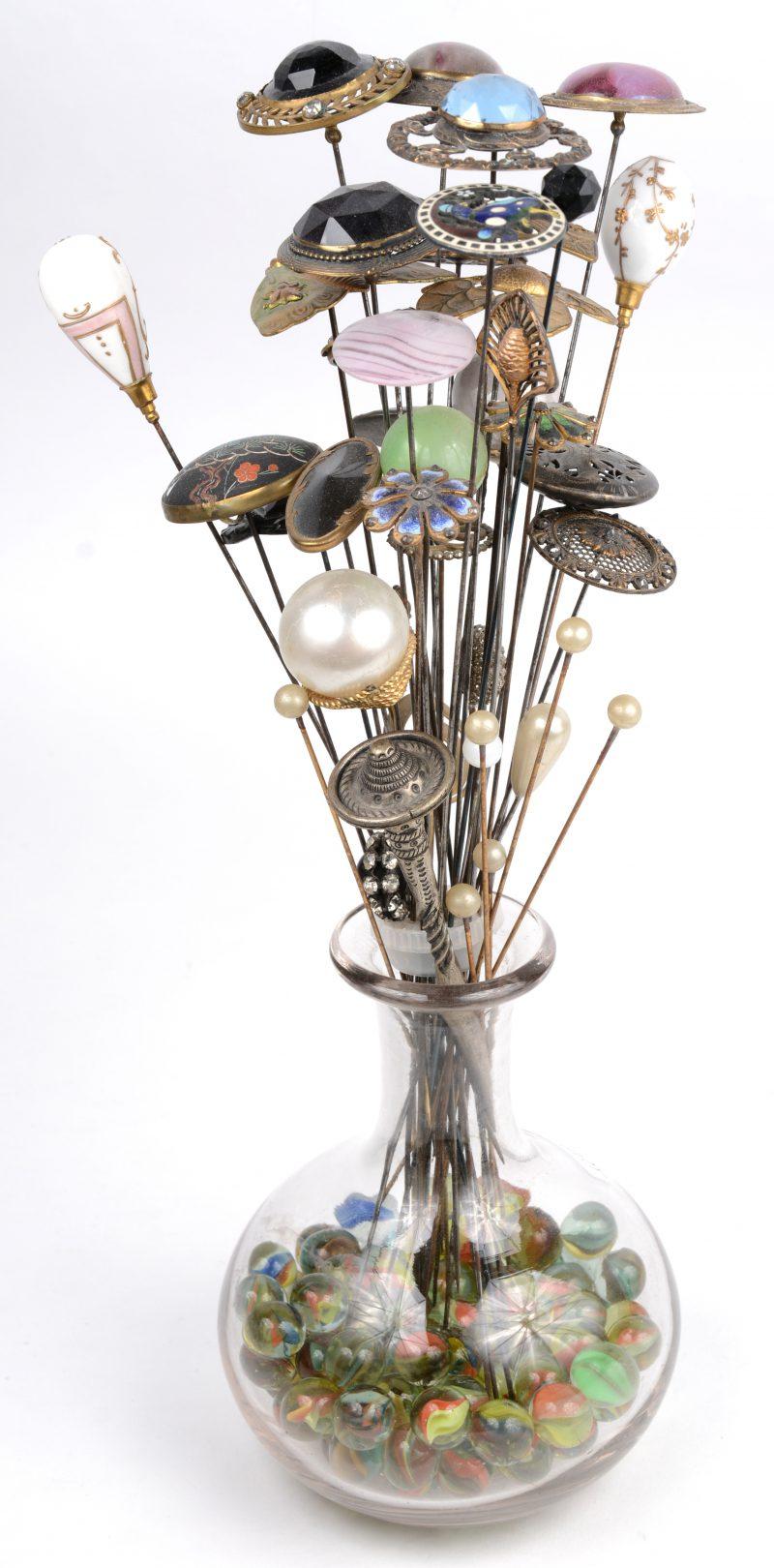 Een leuke collectie van een dertigtal hoedenspelden uit de belle époque, versierd met gegraveerd koper, halfedelstenen, parels enz enz. Gepresenteerd als een bloementuil in een glazen karafje verzwaard met knikkers.