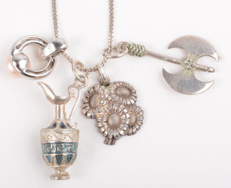 Een zilveren ketting met vier hangers, één bezet met een parel.