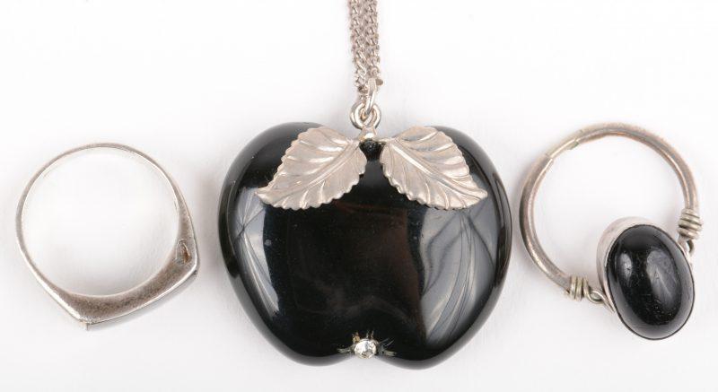 Een zilveren ketting met met zwarte hanger van gite en twee bijpassende ringen.