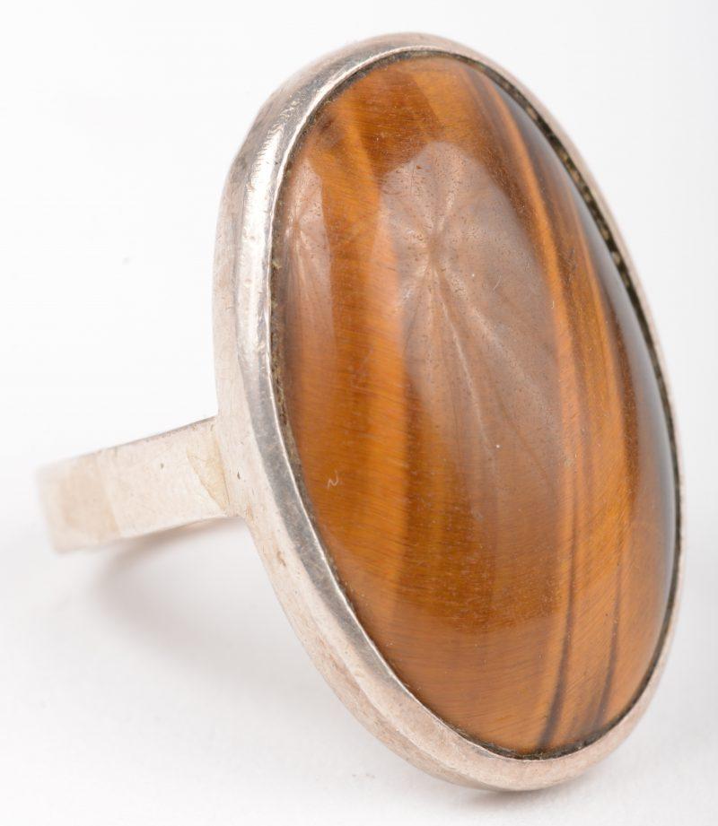 Een zilveren ring bezet met tijgeroog.