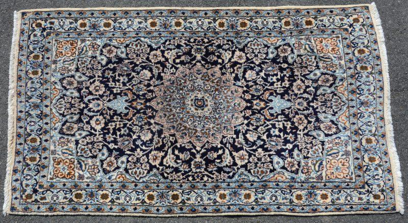 Een handgeknoopt Perzisch karpet van wol en zijde.