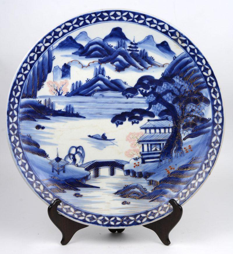 Een sierschotel van Aritaporselein met een blauw op wit landschapsdecor met vergulde en gekleurde details. Met blindemerk onderaan. Tijdperk Taisho.