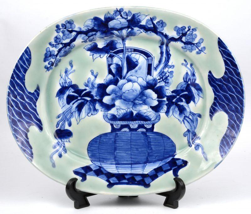 Een ovale porseleinen schotel met een blauw decor van een bloemenvaas op celadonkleurige fond. Onderaan gemerkt.
