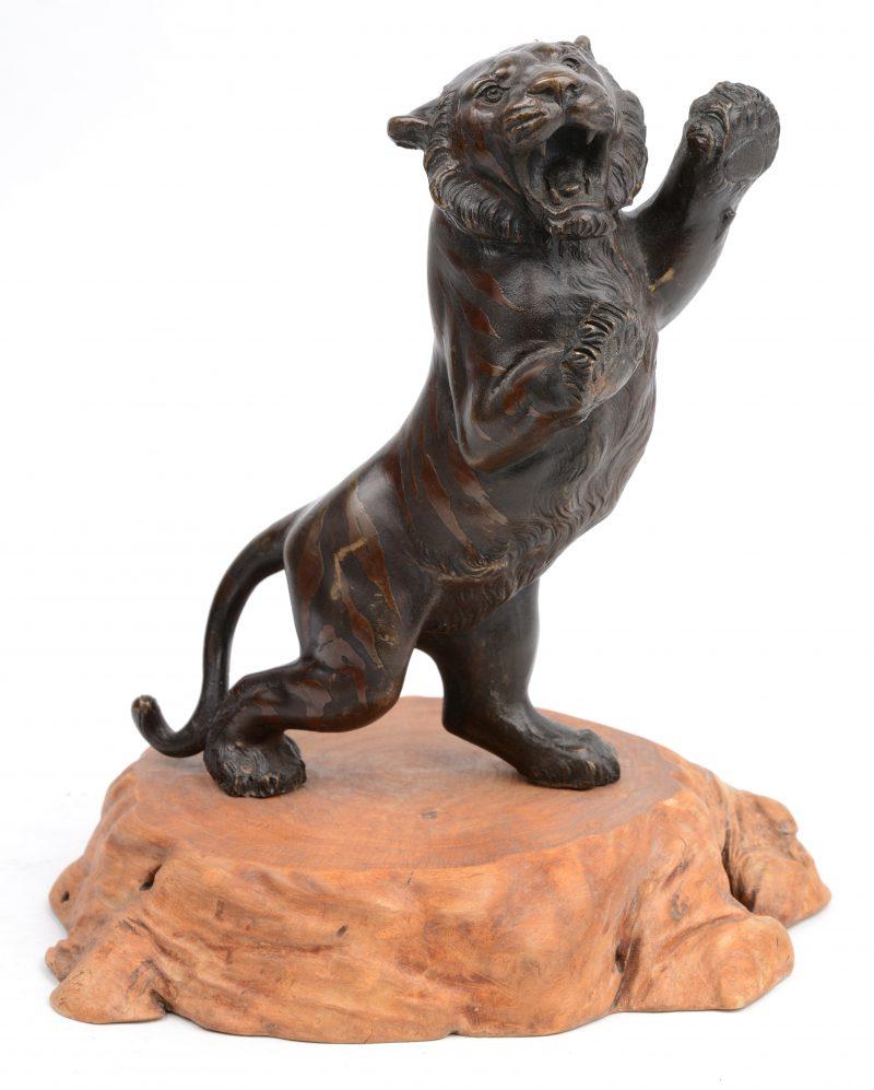 Een brullende tijger van Japans brons op een houten voetstuk. Tijdperk Meji.