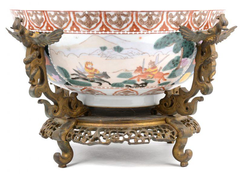 Een grote kom van meerkleurig Japans porselein met een decor van krijgers. In antieke bronzen houder.