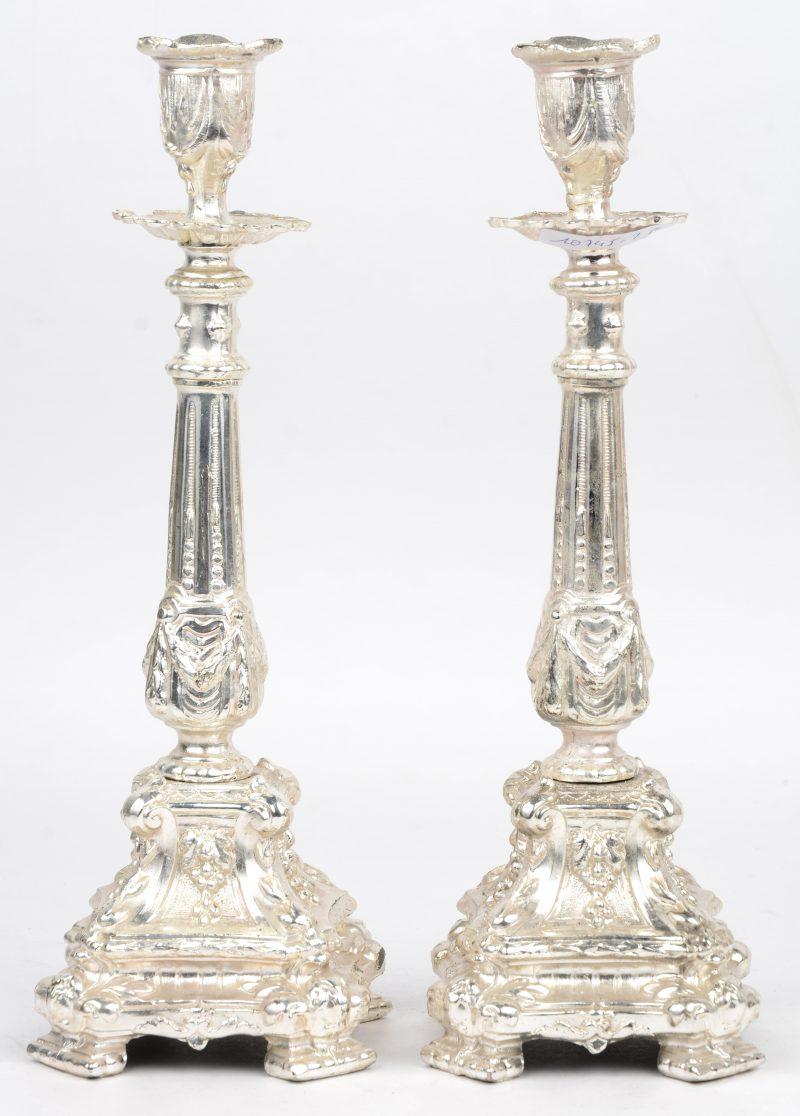 Een paar verzilverd messingen kandelaars in barokke stijl.