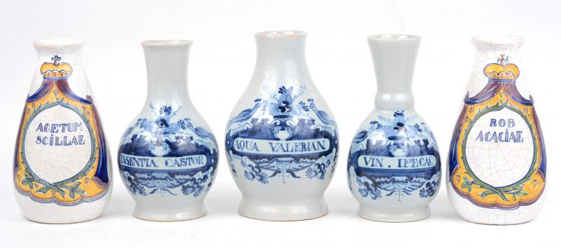 Een stelletje van vijf aardewerken apothekerspotjes, waarbij drie met blauw en wit decor en twee meerkleurig. Apocrief merk van De Drie Klokken onderaan.