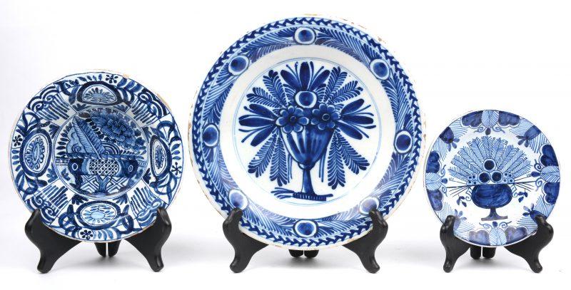 Een lot van drie verschillende Delfts aardewerken bordjes, waarbij twee met bloemen en één met pauwstaartdecor. XIXe eeuw.