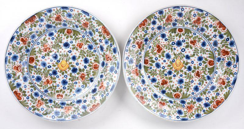 Twee grote sierschotels van meerkleurig aardewerk. Onderaan gemerkt 'C B'.