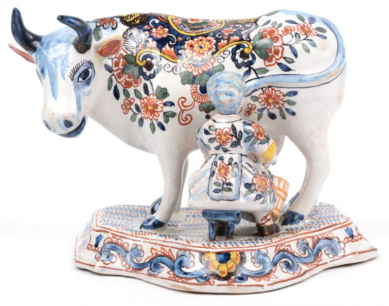 Een melkvrouwtje met koe van meerkleurig Delfts aardewerk. Restauratie aan een hoorn en een voetje en een pootje van het krukje manco. Gemerkt van Dextra onderaan.