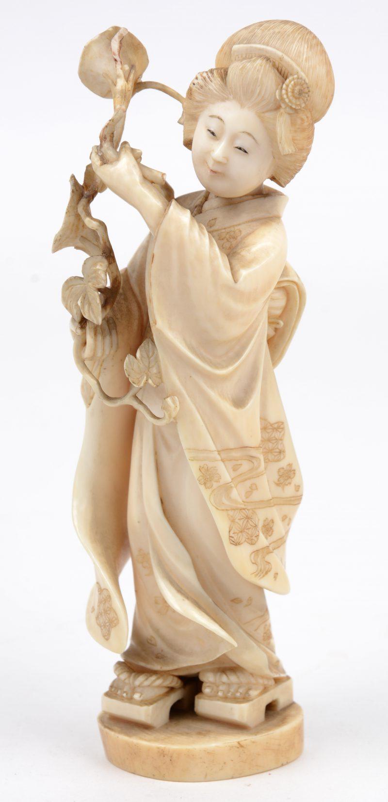 Een fijn gesculpteerde ivoren geisha. Japans werk, eerste helft XXe eeuw. Onderaan gemerkt met stempel.