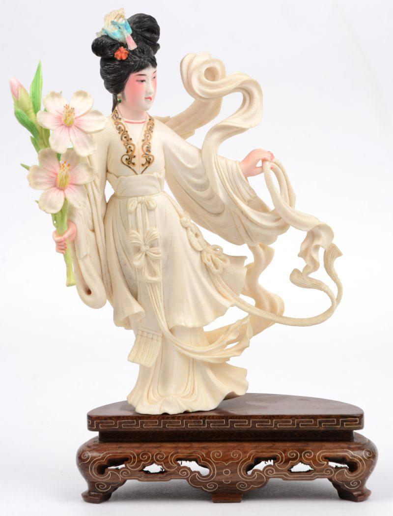 """""""Vrouw met bloemen"""". Een fijn gesculpteerd en gepolychromeerd ivoren beeldje op houten sokkel. China, medio XXe eeuw."""