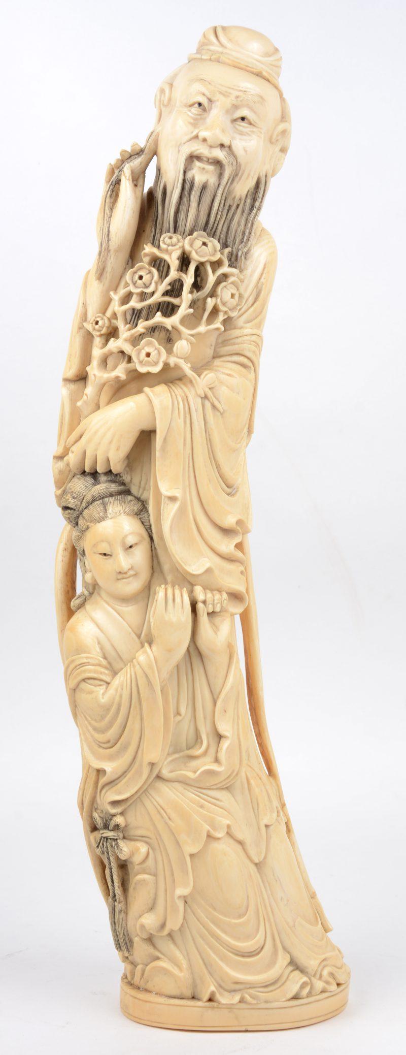 """""""Oude wijze met vrouw"""". Een gesculpteerd ivoren beeld. Onderaan gesigneerd. China, begin XXe eeuw. Instrument manco"""