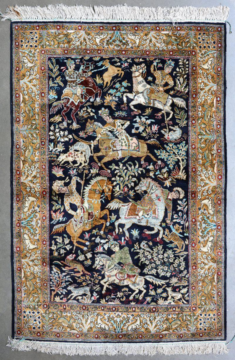 Een handgeknoopt Perzisch kleedje van zijde met een jachtscène in het decor.