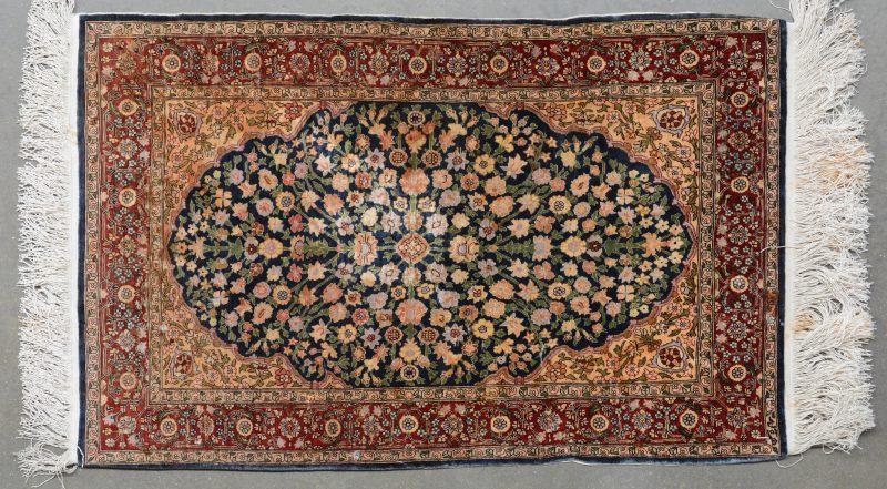 Een handgeknoopt Perzisch kleedje van zijde met een centraal bloemenmedaillon.