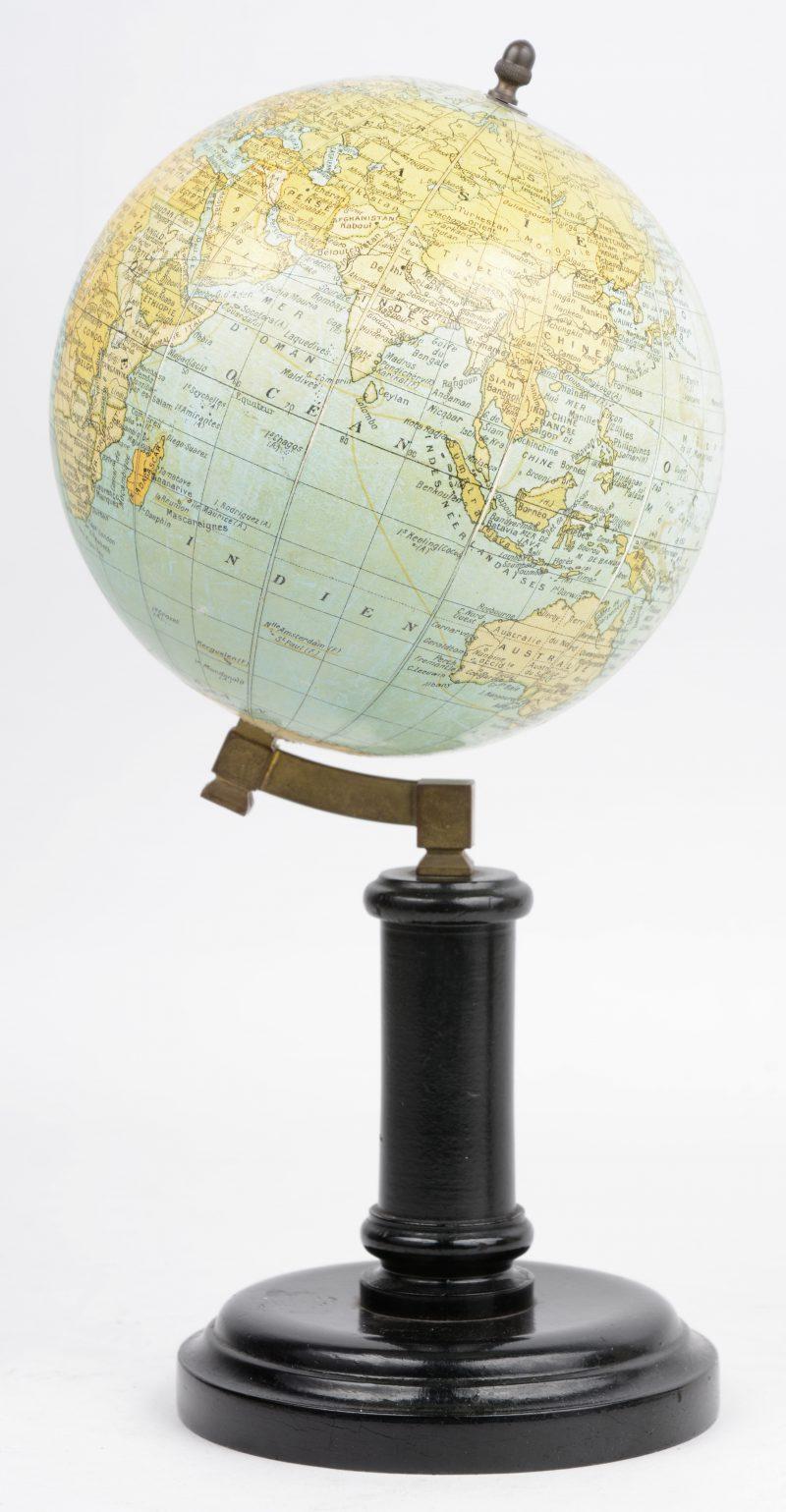 Een kleine wereldbol op zwartgelakte houten voet. Gemerkt.