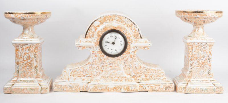 Een driedelig aardewerken kaststel, bestaande uit een pendule en twee cassolettes.