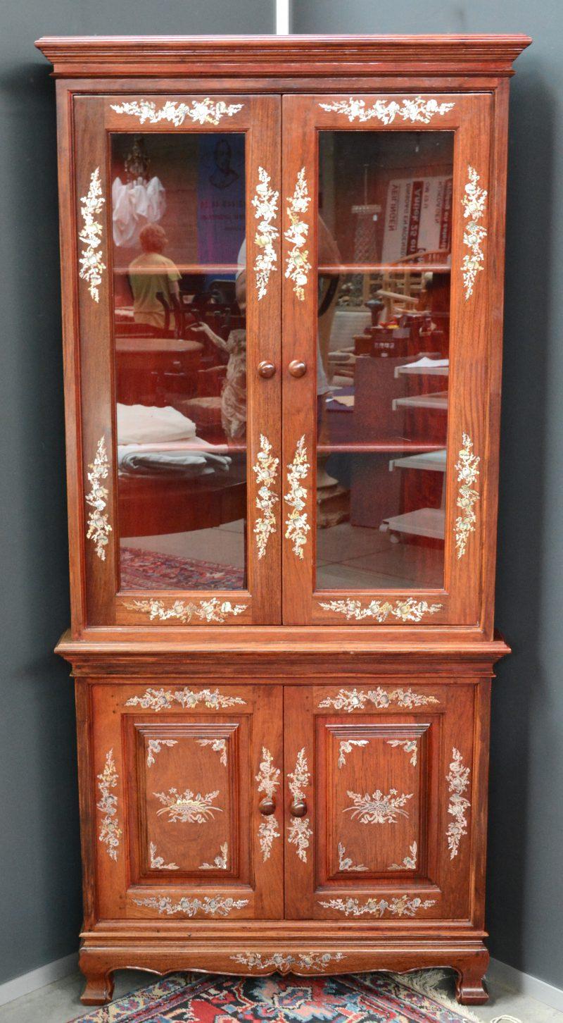 Een Chinees hardhouten hoekvitrine, versierd met ingelegde versieringen van parelmoer.