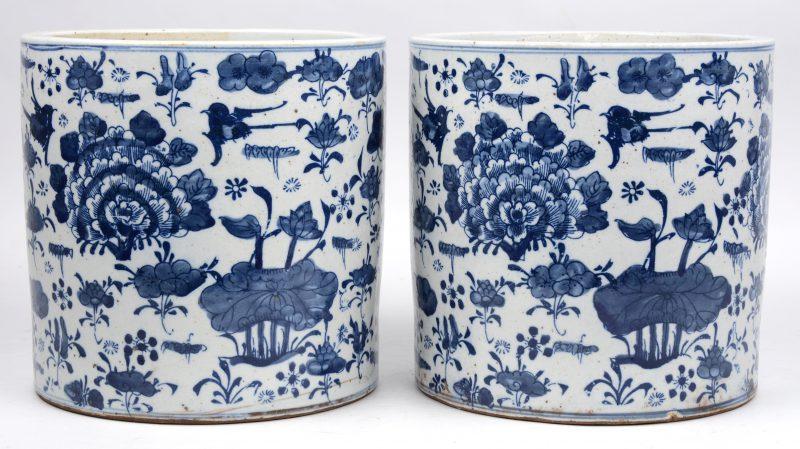 Een paar cilindervazen van Chinees porselein met een blauw op wit bloemen- en plantendecor.