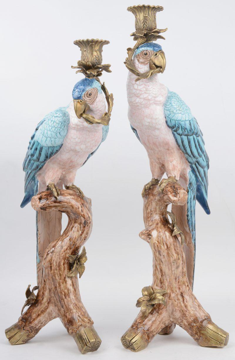 Een paar kandelaars van brons en meerkleurig porselein in de vorm van papegaaien.