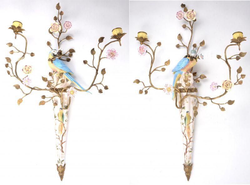 Een paar kandelaars van meerkleurig porselein en messing, opgebouwd uit een sierstuk, getooid met een papegaai en met twee lichtpunten in de vorm van plantenranken met porseleinen bloemen. Apocrief gemerkt achteraan.