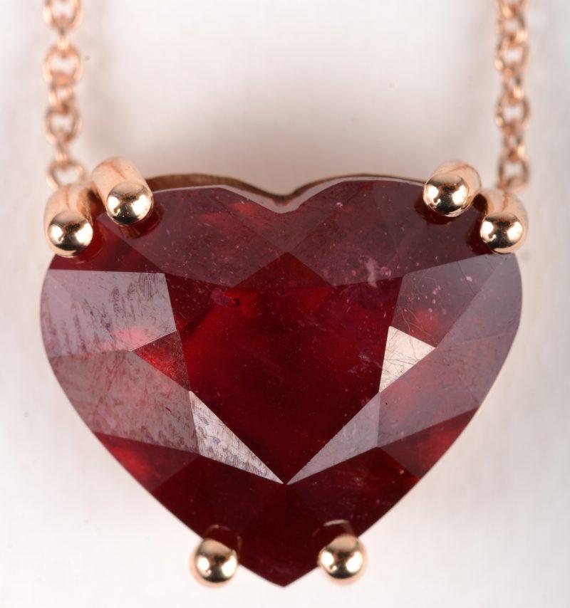 Een 18 K roze gouden ketting met hanger bezet met een hartvormige behandelde robijn van +- 8,20 ct.