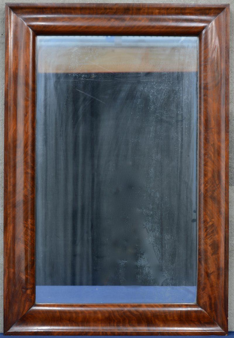Een rechthoekige spiegel in mahoniehouten lijst.