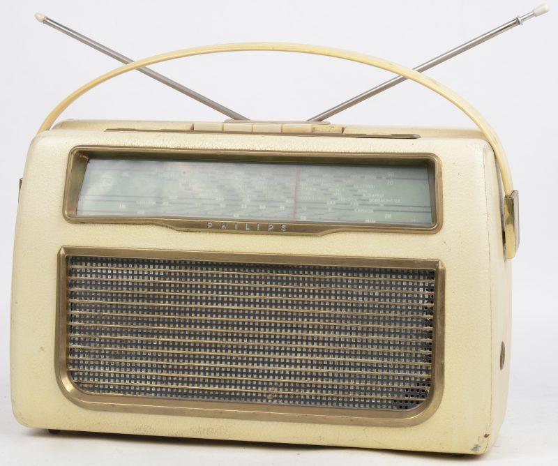 Een draagbare radio in beklede houten kast. Jaren '50.