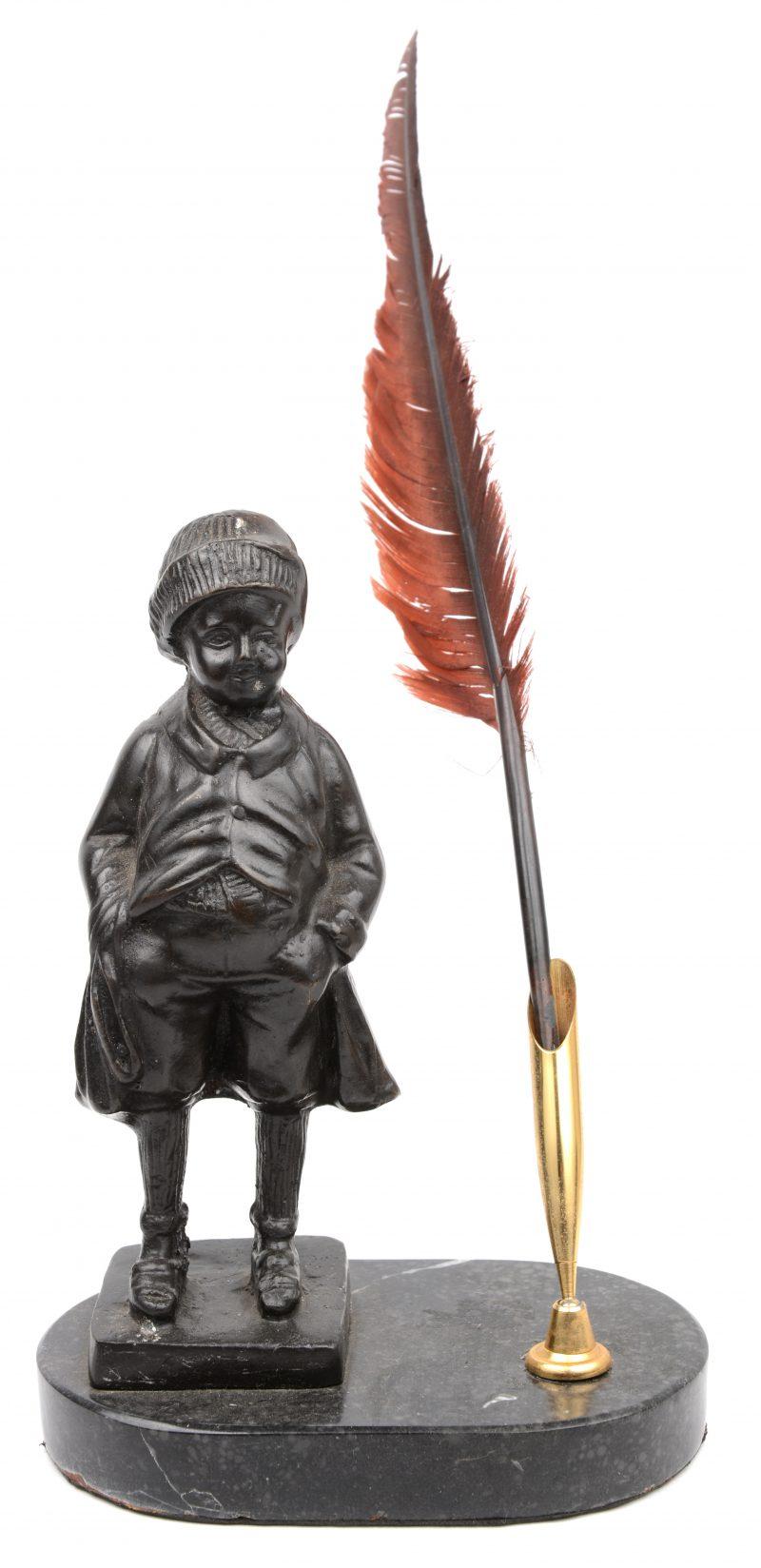 Een pennenhouder, getooid met een bronzen beeldje en op een granieten sokkel.