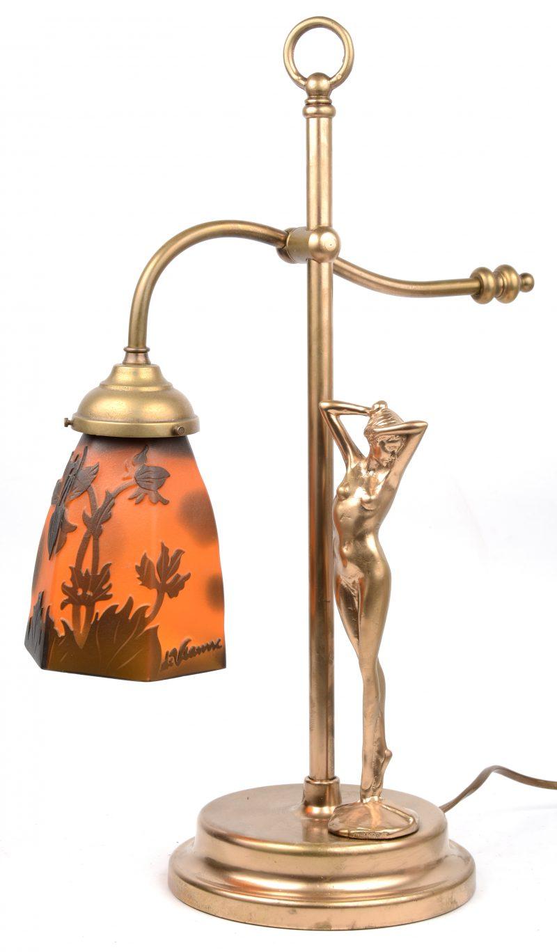 Een messingen tafellampje met glazen kapje en getooid met een vrouwelijk naakt.