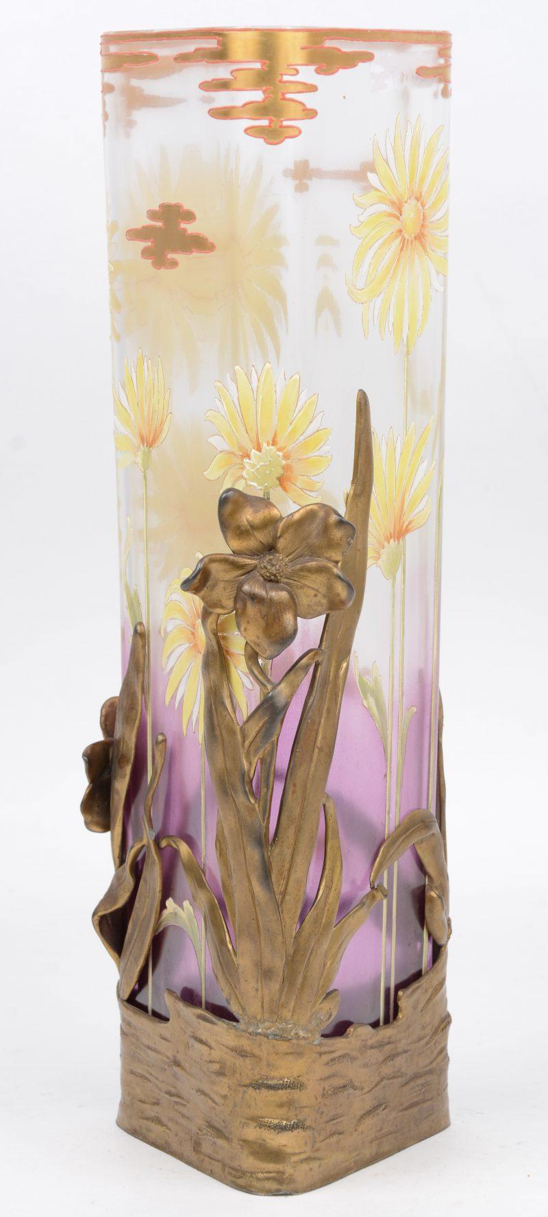 Een driehoekige glazen vaas met een meerkleurig bloemendecor en in messingen montuur. Tijdperk art nouveau. Het montuur gemerkt 'Vanhauten'.