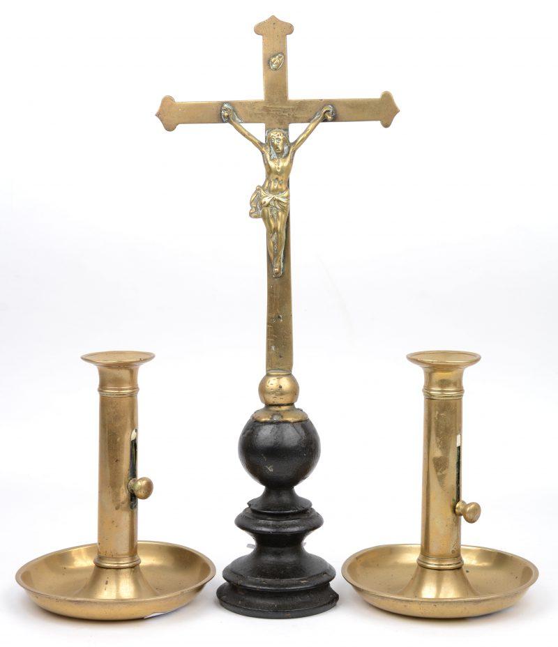 Een kruisbeeldje van koper (met letsel aan de gedraaide houten sokkel) en twee messingen kandelaars.