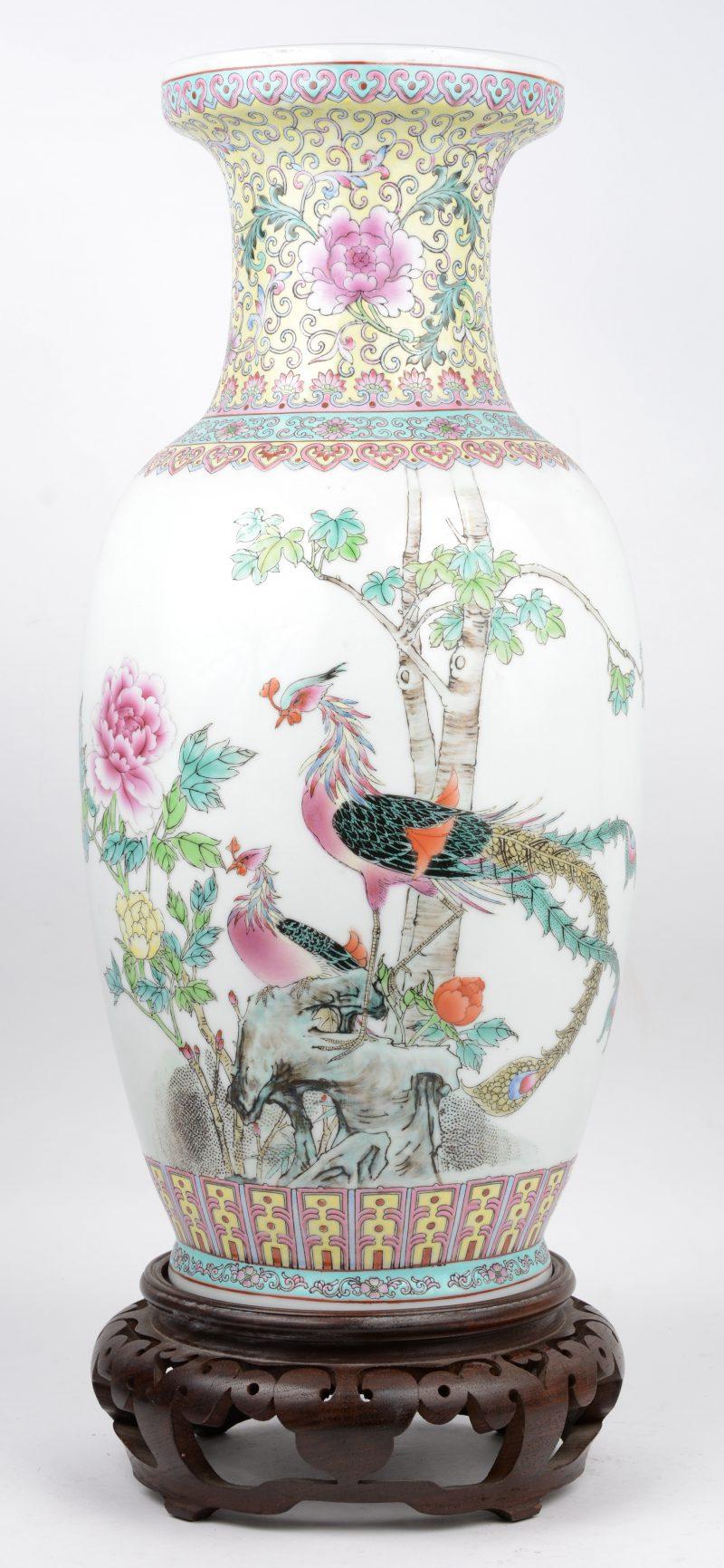 Een vaas van Chinees porselein met een decor van pauwen en pioenen. Met houten sokkel.