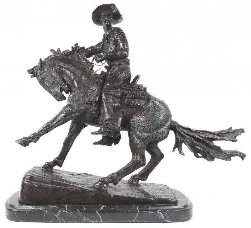 """""""The Cowboy"""". Ruiter te paard. Bronzen beeld naar het werk van Frederic Remington. Op marmeren voetstuk. Recente geut. (Kleine restauratie)"""