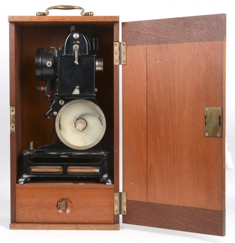 Een antieke projector in houten kastje en met toebehoren in het laatje. Incompleet en glaasje gebroken.