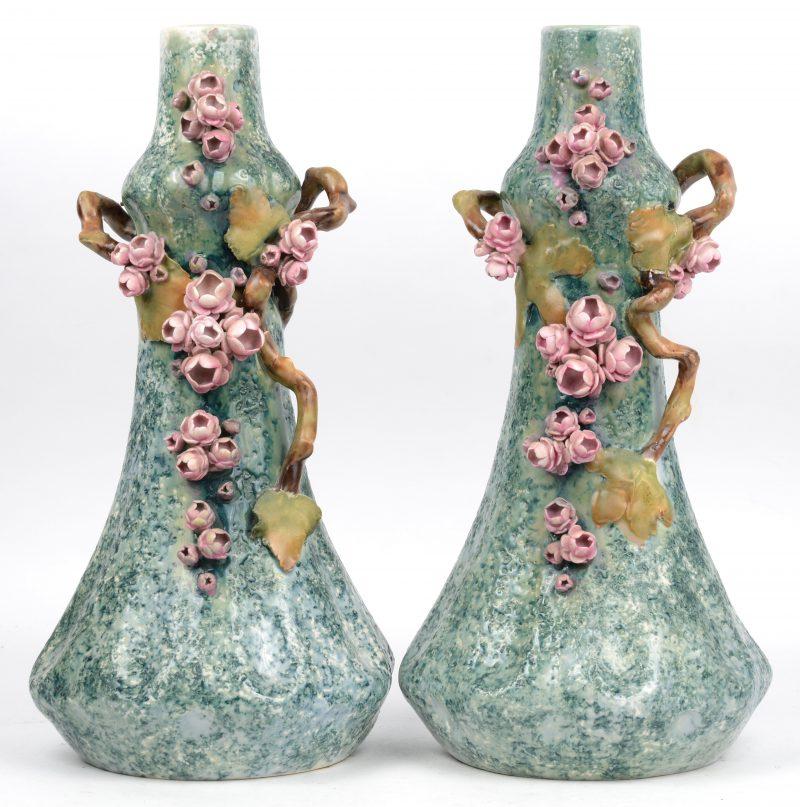 Een paar merkwaardige vazen van geglazurd aardewerk met bloesems in hoogreliëf. Gemerkt 'Austria' onderaan. Toegeschreven aan Riessner, Stellmacher & Keller. Omstreeks 1900.