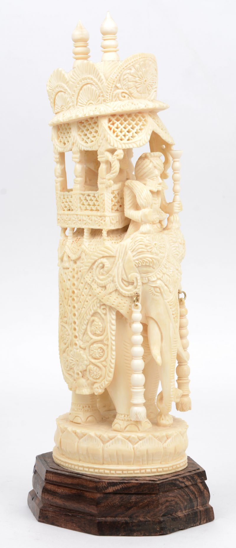 Een rijkelijk uitgewerkte olifant met personages in een opengewerkt rijtuig. Indisch werk. Op houten sokkel.