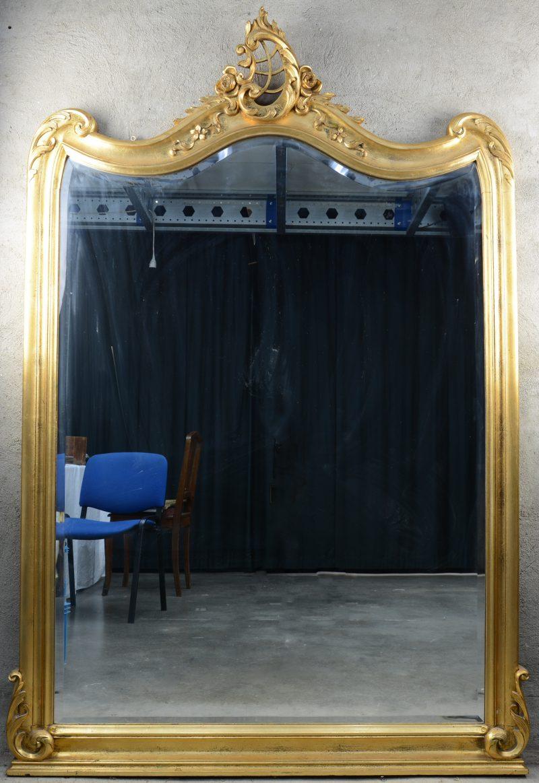 Een vergulde spiegel in Lodewijk XV-stijl. Bovenaan versierd met een rocaille.