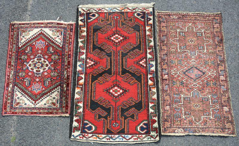 Een lot van drie kleine handgeknoopte wollen karpetjes.