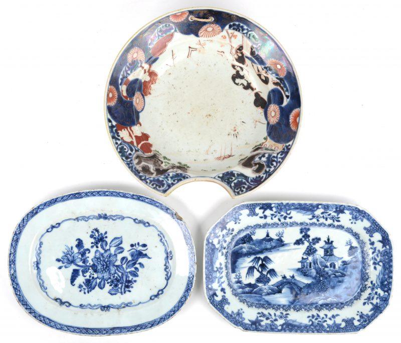 Een lot porselein, bestaande uit een ovaal en een achthoekig schoteltje van blauw en wit Chinees porselein (randslijtage) en een scheerbekken van Imari porselein, met afgesleten decor. Omstreeks 1800.