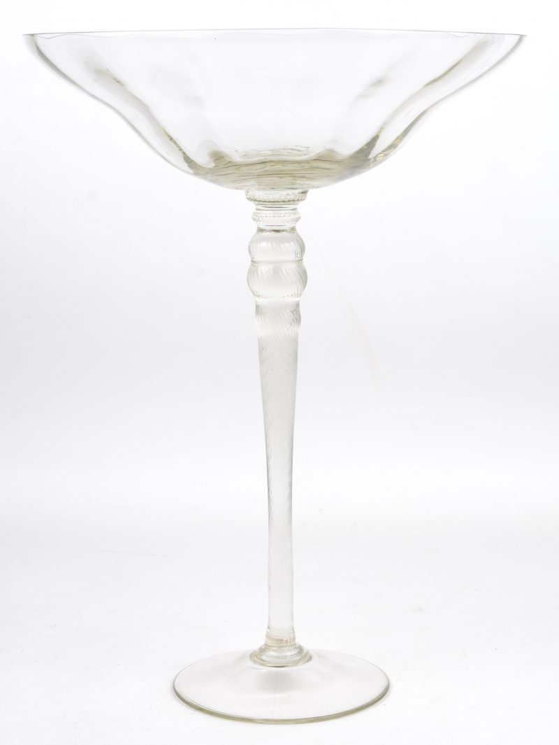 Een kleurloze glazen schaal op hoge voet.