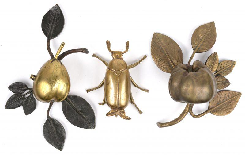 Drie vol messingen (as)bajkes, waarbij twee in de vorm van een vrucht en één in de vorm van een kever.