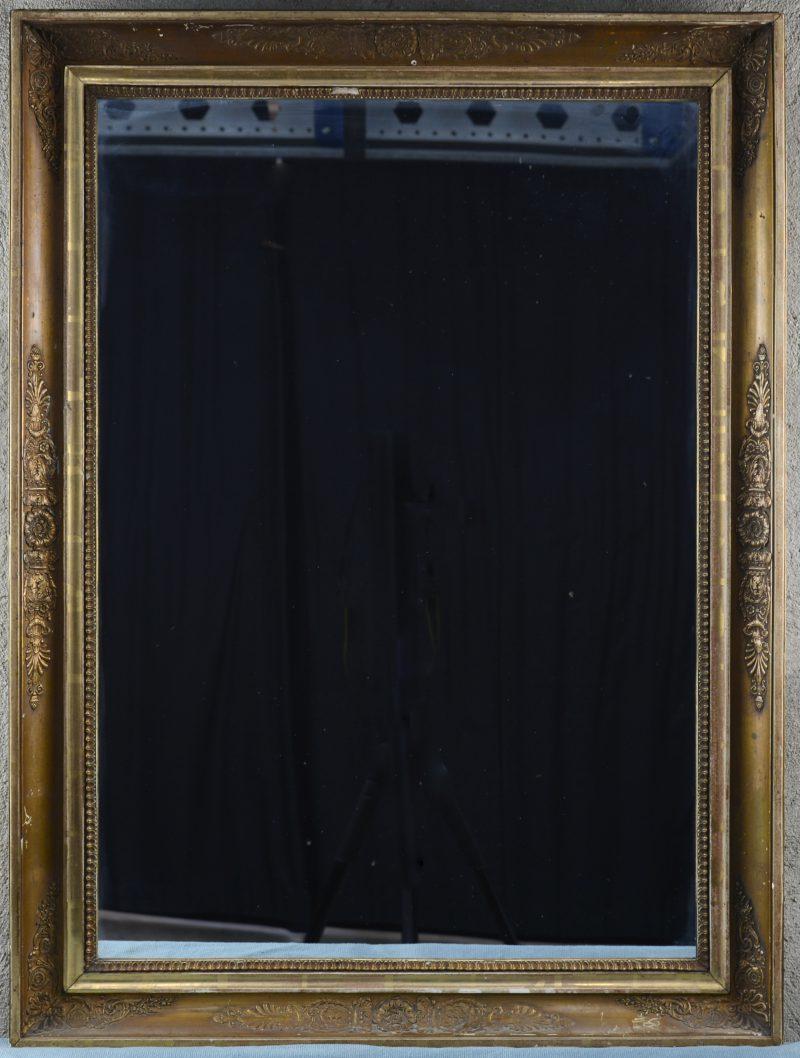 Een spiegel in verguld houten lijst, versierd met barokke motieven.