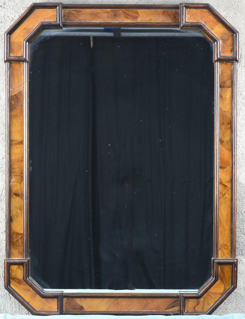 Een spiegel in houten lijst met notenhoutfineer.