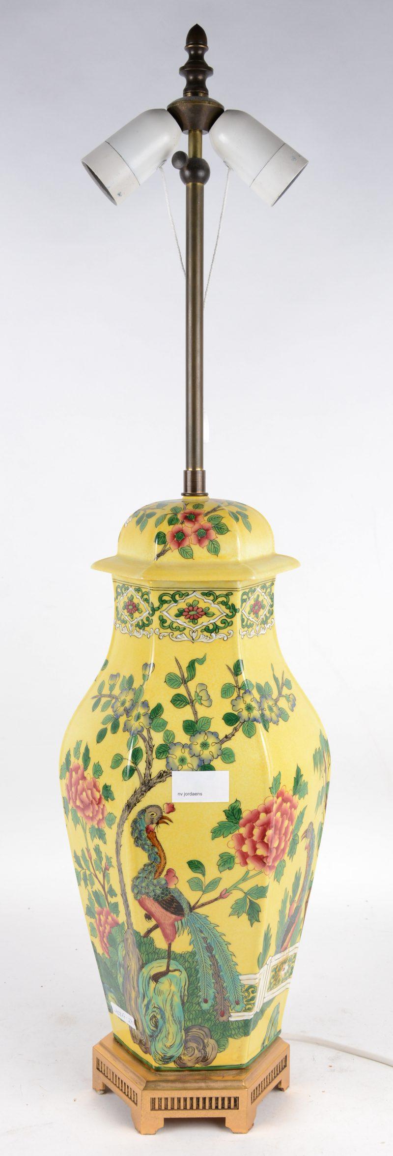 Een zeshoekige lampenvoet van Chinees porselein met een meerkleurig decor van pauwen en bloesems op gele achtergrond.