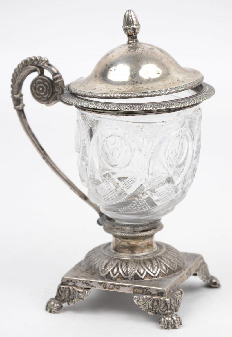 Een mosterdpotje van geslepen kleurloos kristal in zilveren montuur. Belgisch gekeurd, tweede gehalte (800/1000), maker F.D.
