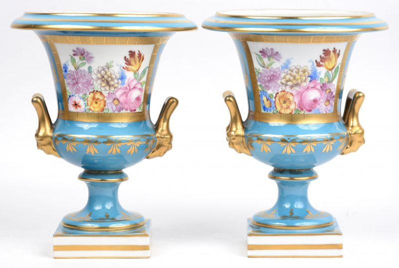 Een paar siervaasjes op voet van Saksisch porselein met een verguld decor op blauwe fond. Onderaan gemerkt.